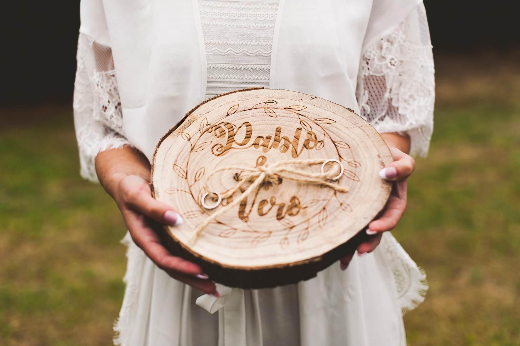 La novia sujetando el portaalianzas, con el logo de la boda tallado en madera.