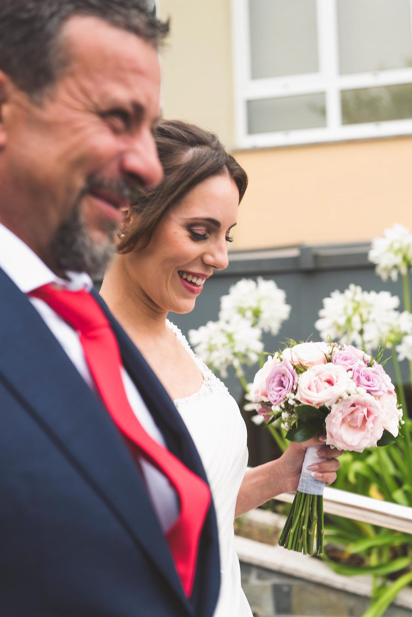 La novia sonriendo mientras llega a la ceremonia con el padrino, su padre.