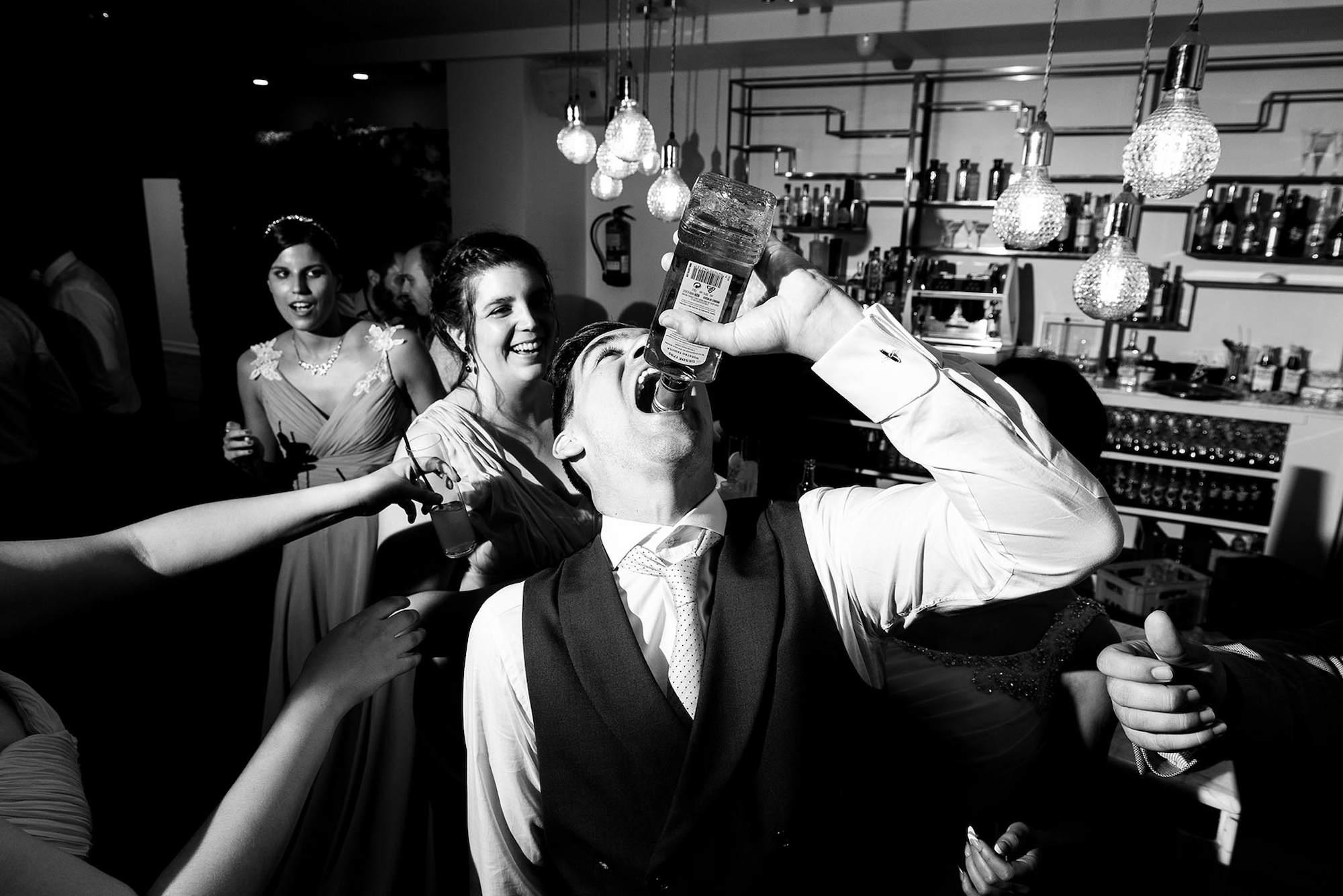 El novio echando un trago durante la fiesta durante el día de la boda.