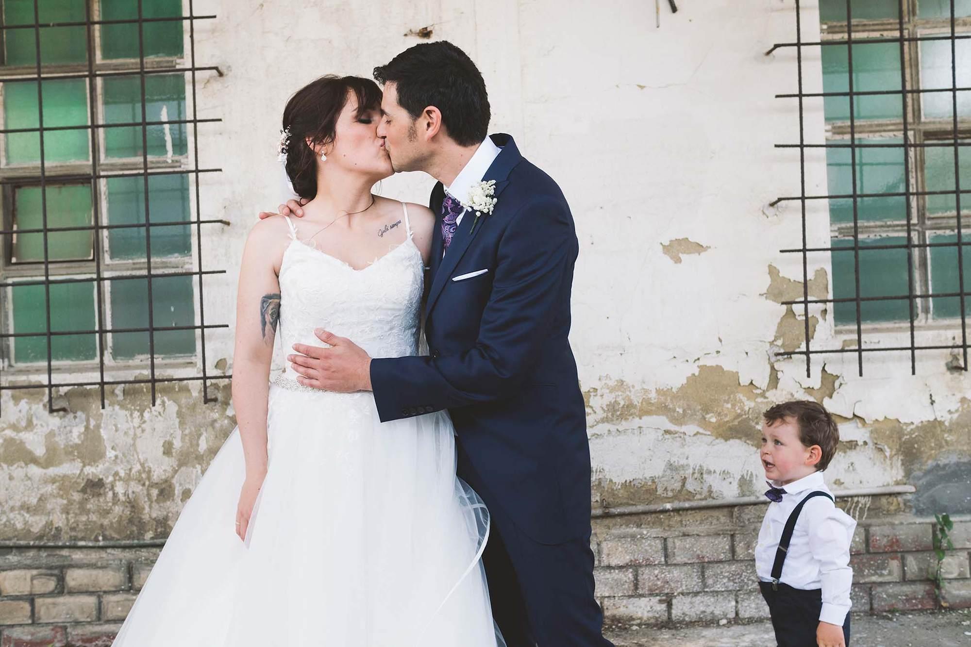 Los novios dándose un beso con su hijo a un lado de la fotografía