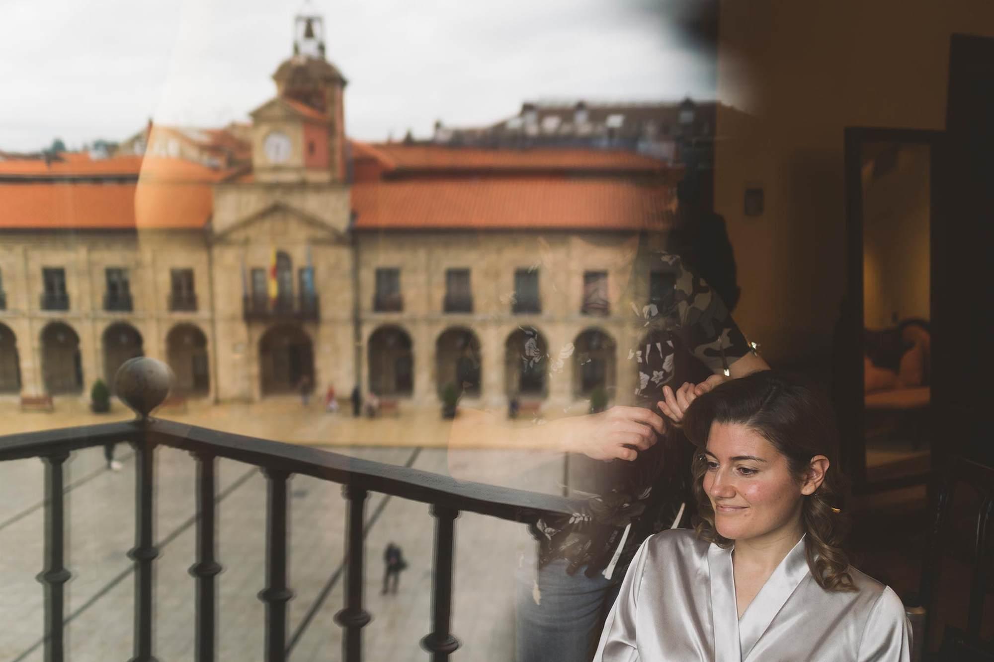 La novia siendo peinada mientras el ayuntamiento de Avilés se refleja en la ventana de su habitación.