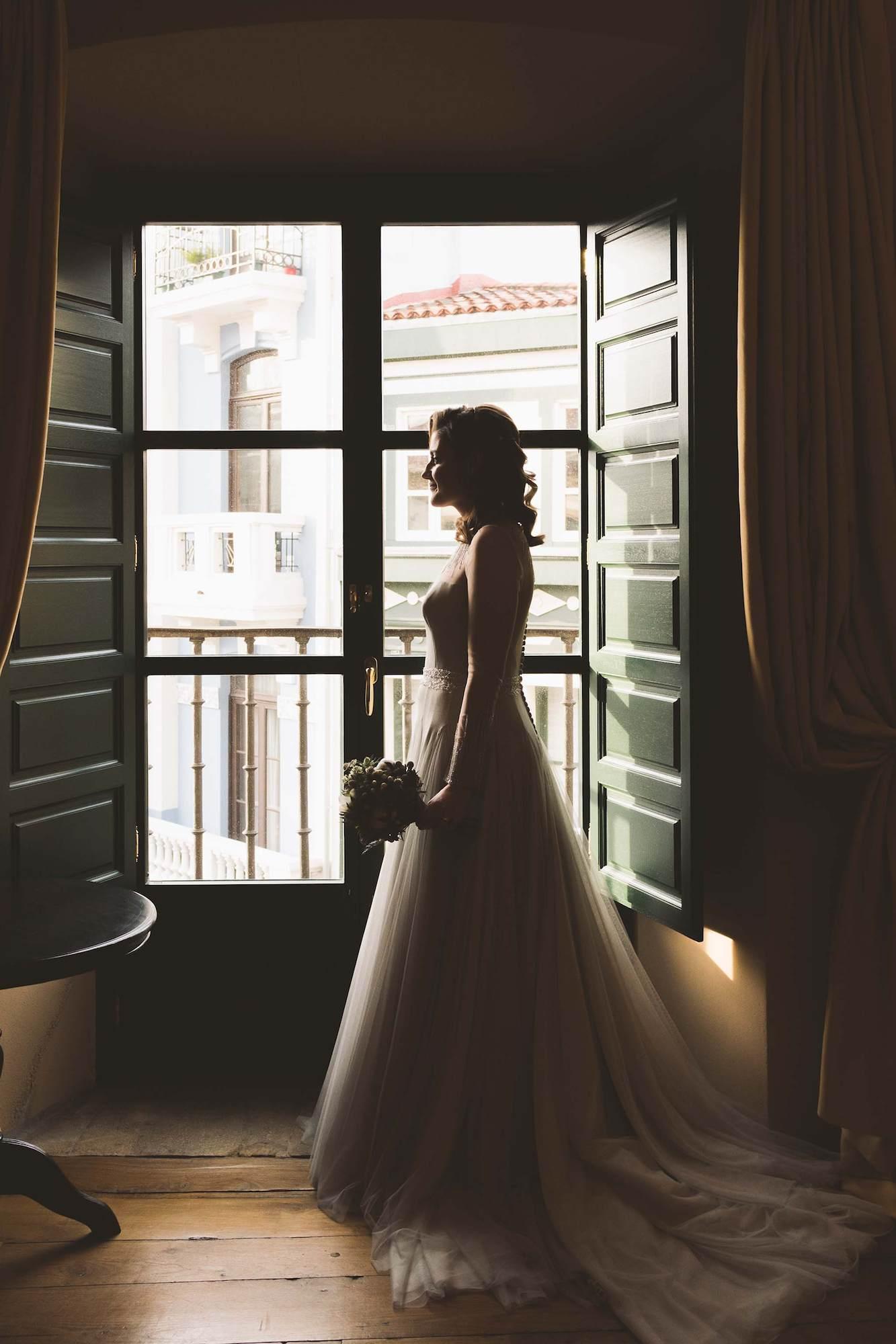 Retrato de la novia en la ventaba de su habitación.