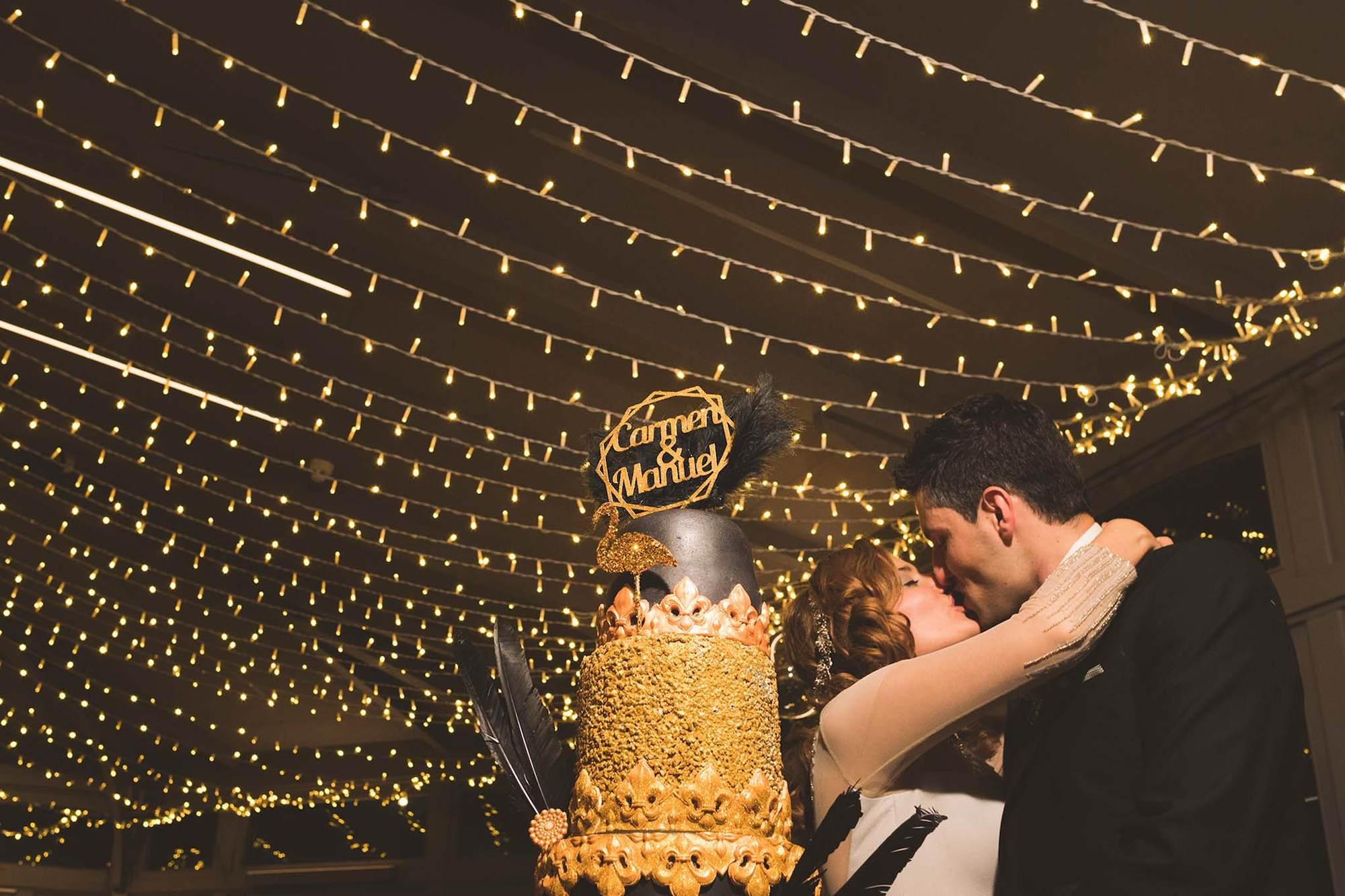 Los novios besándose tras el corte de la tarta.