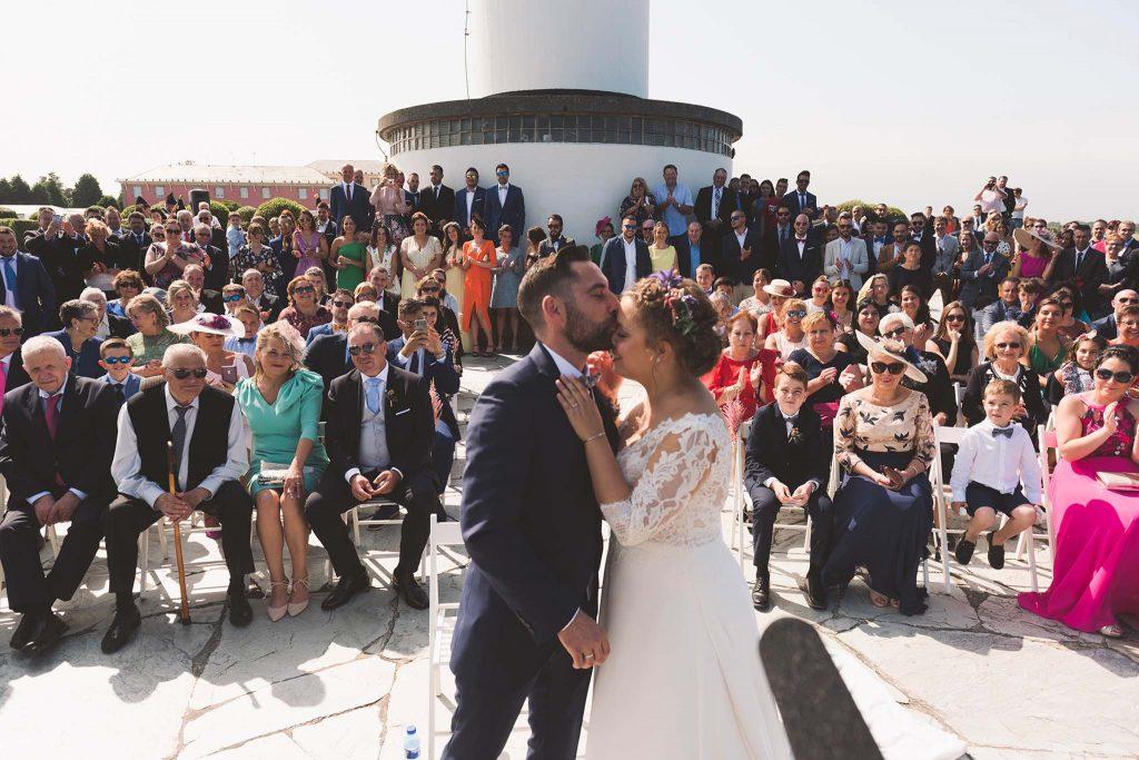 Los novios besándose durante la ceremonia celebrada en el faro de Ortiguera, mientras sus invitados les aplauden