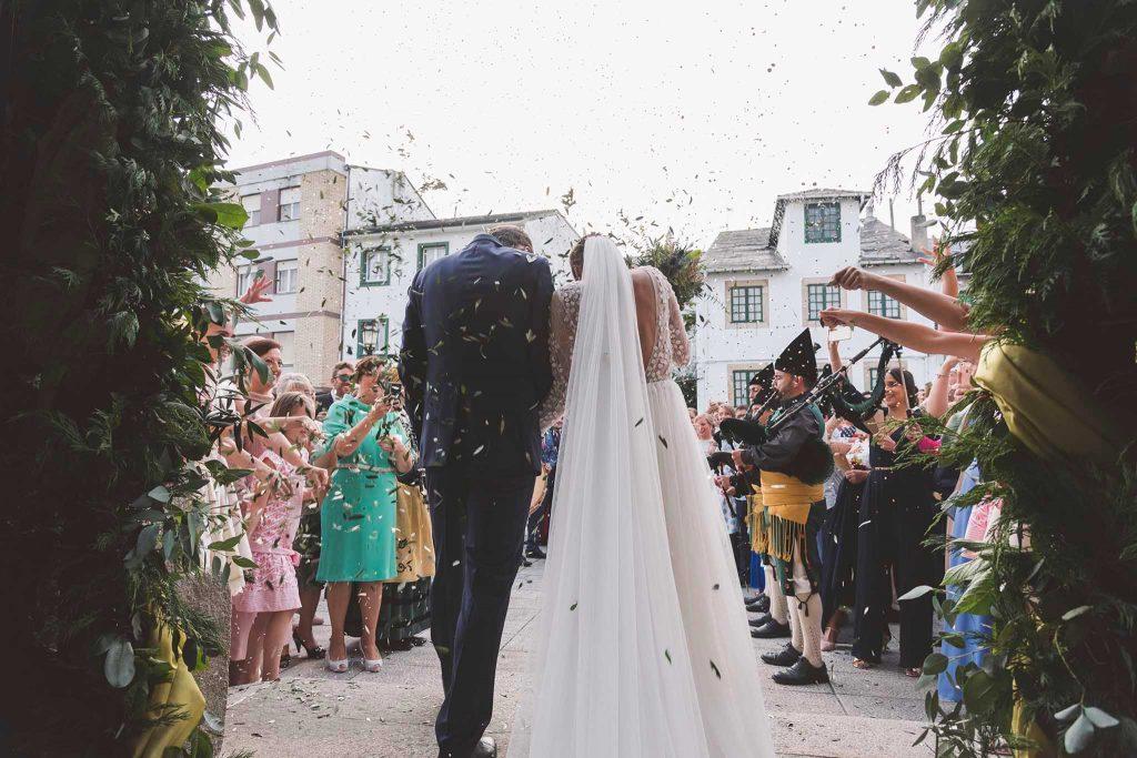La salida de los novios mientras los invitados les arrojan arroz, pétalos y confeti.